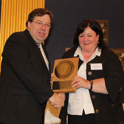 """Ms. Ann McHugh from the HSE receives the award for """"Sexual Assault Care"""" from an Taoiseach."""